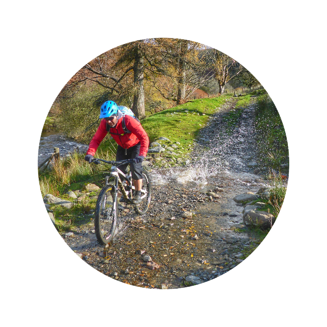 Mountain biking through a stream with corporate discounts for cycling holidays